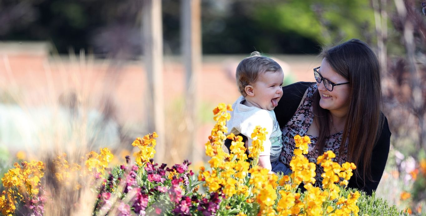 An image of a mother and baby exploring the flower beds in the Walled Garden
