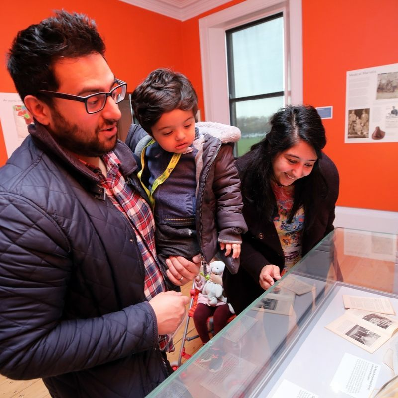 Family Looking At Items On Display In Preston Park's Gallery