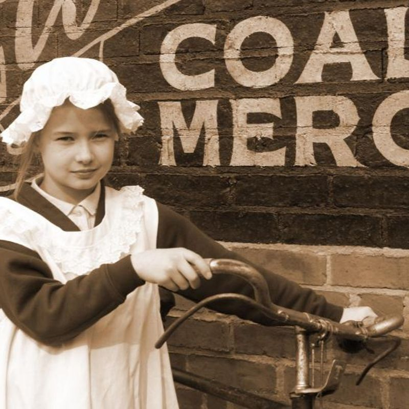 Girl Wearing Victorian Cosume Holding An Old Fashioned Bike