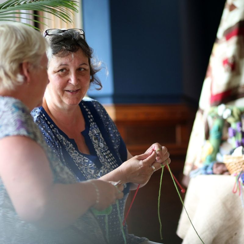 Two Ladies Knitting Together