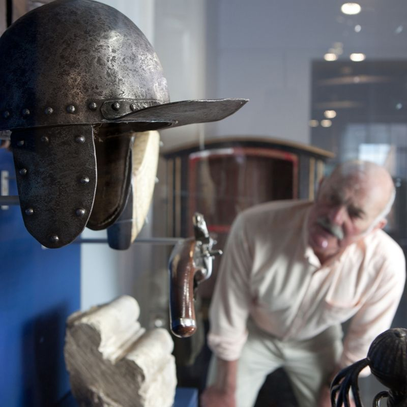 Visitor Looking At Items On Display In A Case Including A Pistol And Viking Helmet