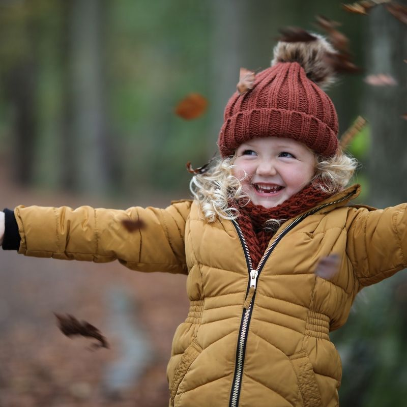 Young Girl Throwing Autumn Leaves In The Air In The Park