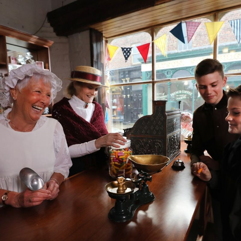Young Boys Being Served Sweets By Two Victorian Ladies In The Old Fashioned Sweet Shop