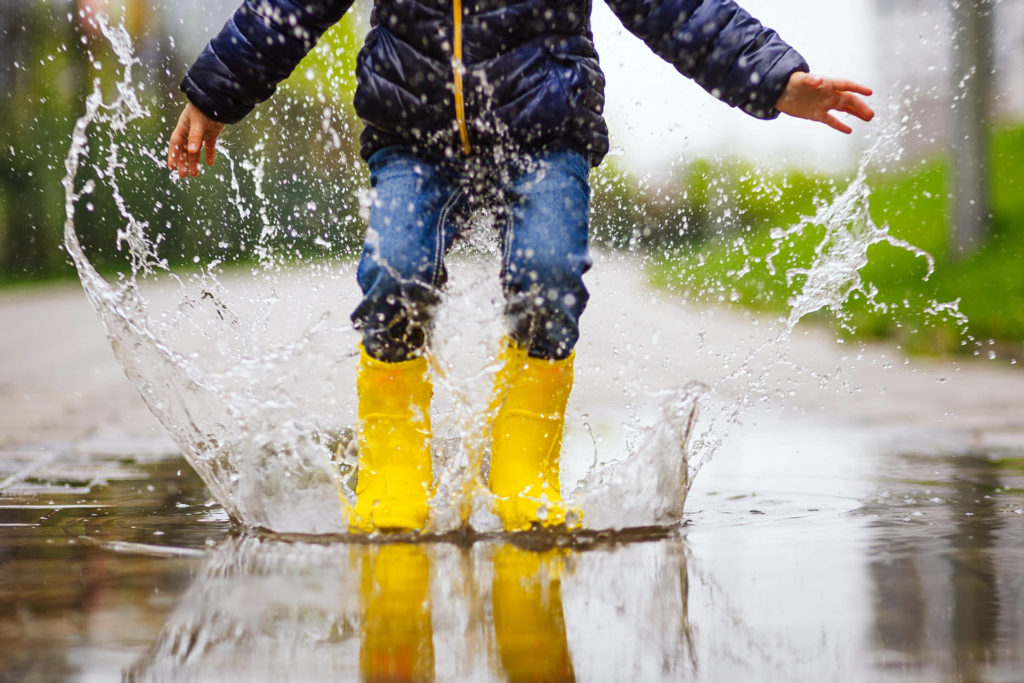 Child Jumping In Puddle On Autumn Walk
