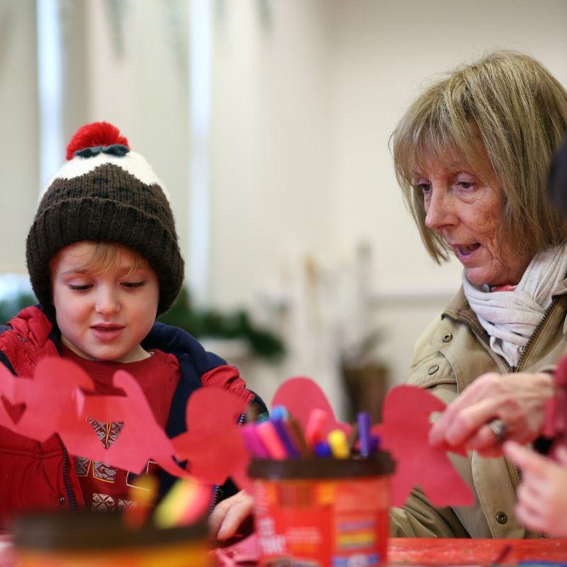 Child And Grandparent Making Christmas Craft