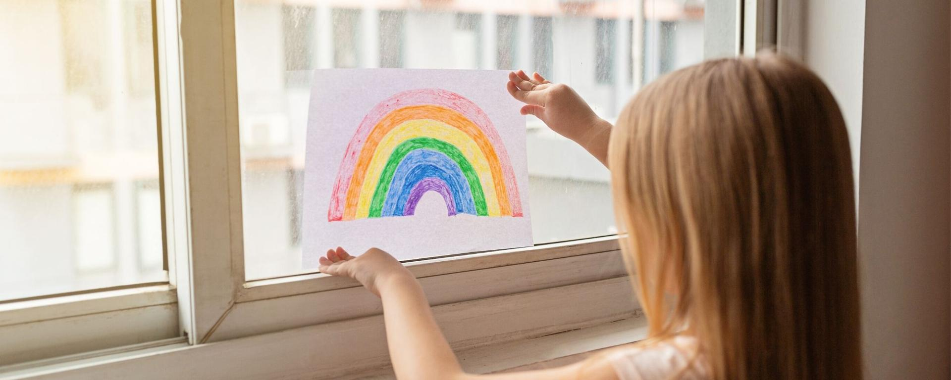 Girl Putting Her Rainbow Picture In The Window.jpeg